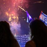 Tel Aviv / Israel -  May 11th 2016: Silhouttes of two girls attending the celebrations of Independence Day and watching the official fireworks at night at Rabin Square in Tel Aviv / Israel