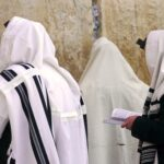 Orthodox Jews wearing tallit shawls are praying with Siddur prayer books at the Western/Wailing Wall or Kotel, holiest site in Judaism; Jerusalem Israel